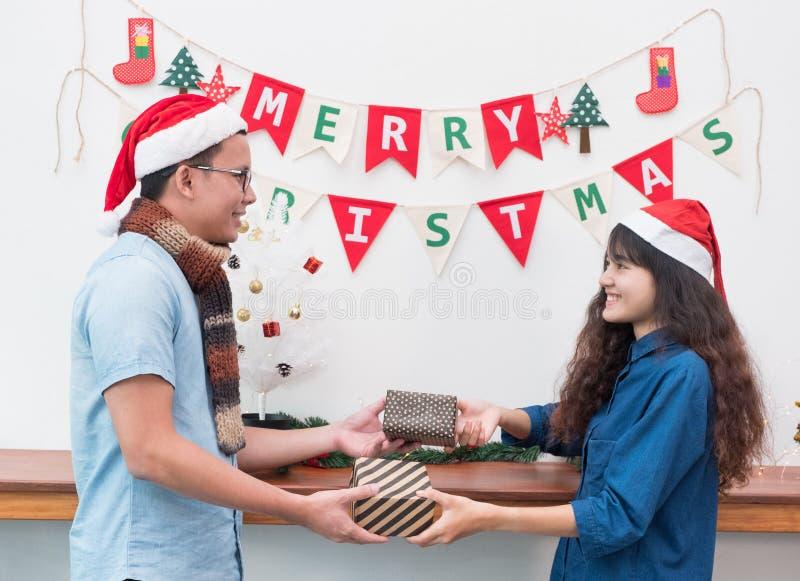 Asiatiska vänpar bär den santa hatten i parti för glad jul och e royaltyfri bild