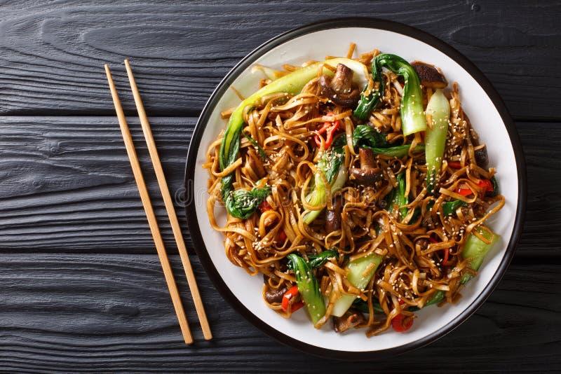 Asiatiska vegetariska matudonnudlar med behandla som ett barn choy bok, shiitakechampinjoner, sesam och pepparnärbild på en platt royaltyfria foton