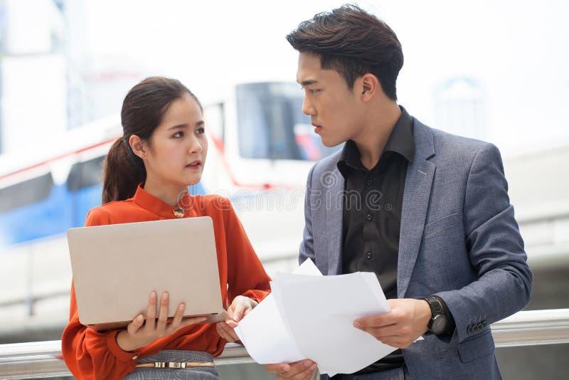 asiatiskt affärsfolk med den Digital bärbara datorn och dokument som tillsammans utomhus diskuterar i möte för stadspartnerarbete arkivbild