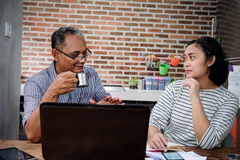 Asiatiskt affärsfolk som har att intressera det hemmastadda kontoret för diskussion royaltyfri fotografi