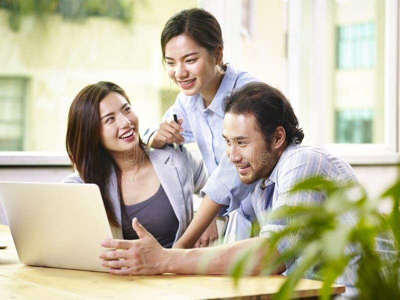 Asiatiskt affärsfolk som tillsammans i regeringsställning arbetar royaltyfri fotografi