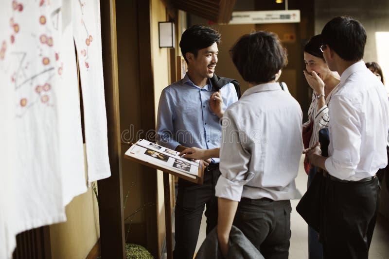 Asiatiskt affärsfolk som ut hänger på den japanska restaurangen fotografering för bildbyråer