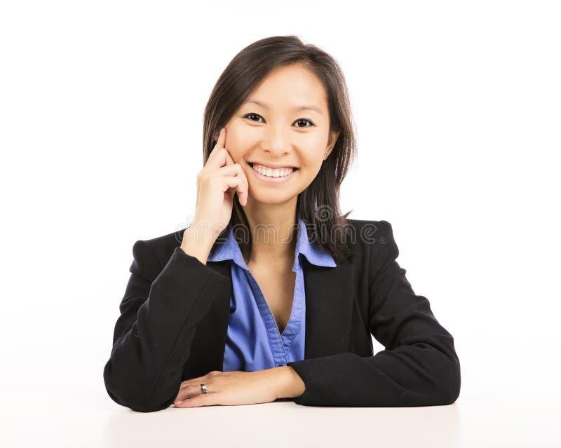 Asiatiskt affärskvinnasammanträde på skrivbordet royaltyfri foto