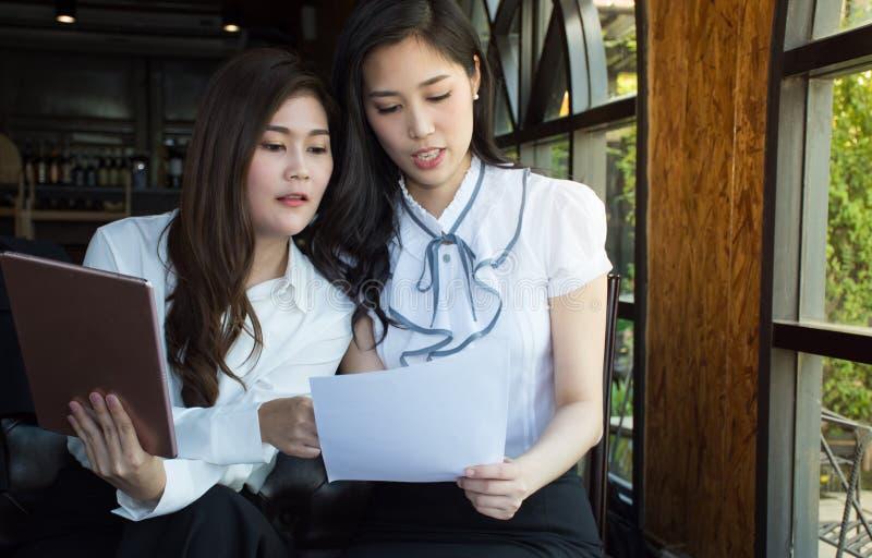 Asiatiskt affärslag som diskuterar dokumentet på den coffee shop-/lagarbetsprocessen royaltyfri foto