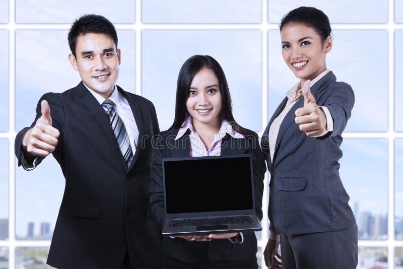 Asiatiskt affärslag som visar den tomma skärmen på bärbara datorn royaltyfria foton