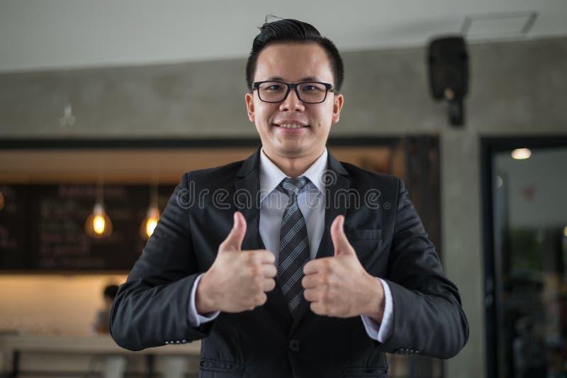 Asiatiskt affärsmanleende och showtumme upp två hand på kontoret, lyckat begrepp royaltyfri foto