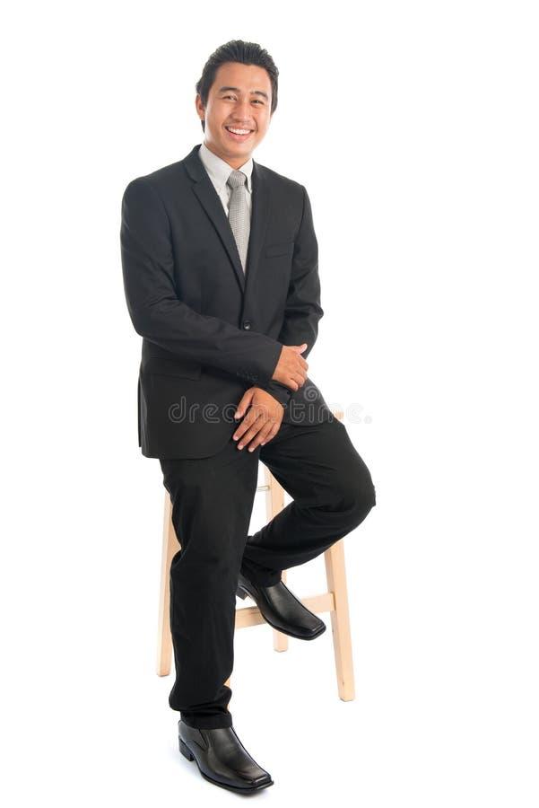 Asiatiskt affärsmansammanträde på stol royaltyfri bild