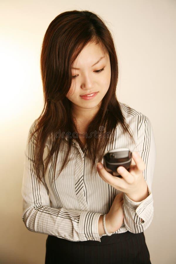 asiatiskt använda för ladykontorstelefon royaltyfri bild