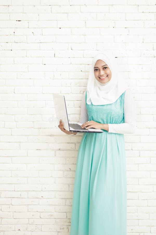 asiatiskt bärande hijabanseende för ung kvinna, medan rymma en bärbar dator arkivfoton