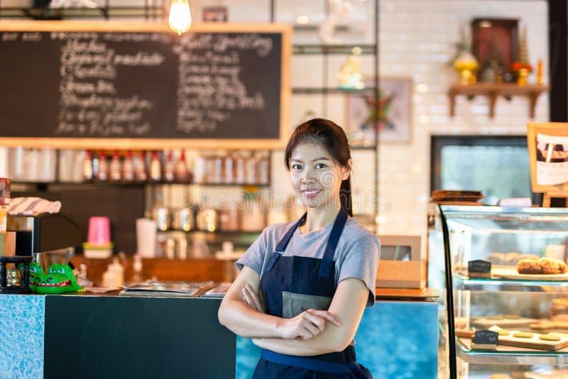 Asiatiskt baristakvinnaanseende med leende på framdel av litet SME för kafé arkivfoto