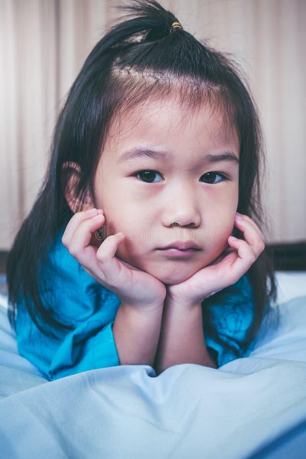 Asiatiskt barn för olycklig sjukdom som medges i sjukhus Inte gör de ser smaskiga royaltyfri bild