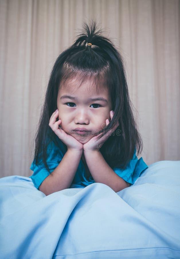 Asiatiskt barn för olycklig sjukdom som medges i sjukhus Inte gör de ser smaskiga royaltyfri foto