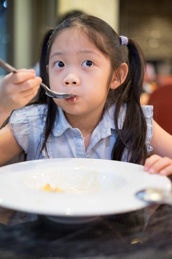 Asiatiskt barn, flicka som läppjar soppa royaltyfri fotografi