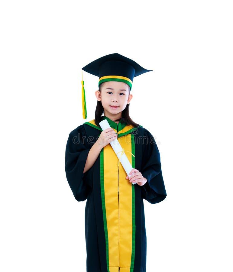 Asiatiskt barn i avläggande av examenkappa och lock som ler och rymmer dipl royaltyfria foton