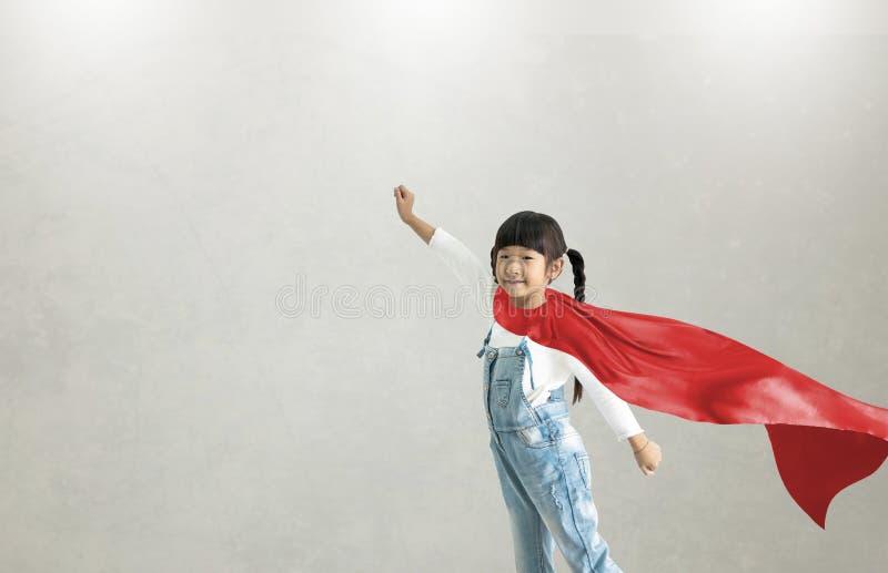 Asiatiskt barn som agerar för att vara superhero Imanigination och framgångbegrepp Idérikt tänka för lek i unge fotografering för bildbyråer