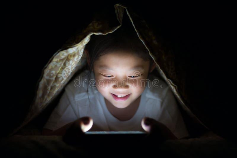 Asiatiskt barn som använder minnestavlaPC i säng på natten royaltyfria foton