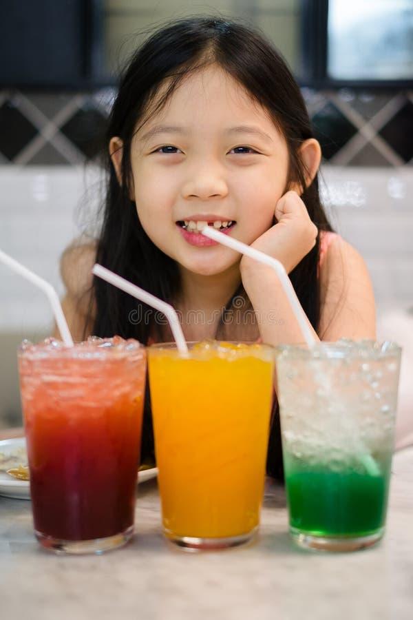 Asiatiskt barn som dricker fruktsaft- eller fruktdrycken från exponeringsglas arkivfoton