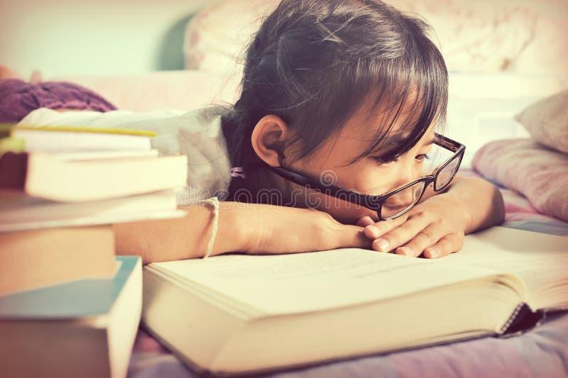 Asiatiskt barn som sover, medan läsa i sängen Flicka med exponeringsglas royaltyfri bild