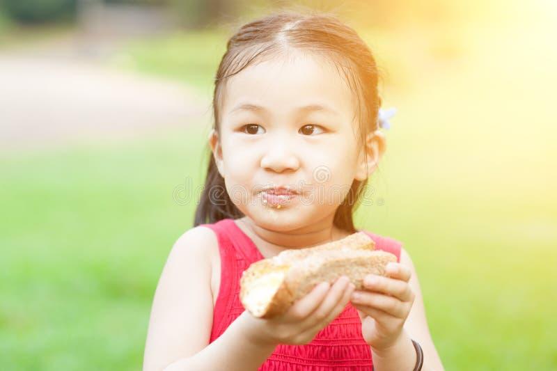 Asiatiskt barn som utomhus äter royaltyfria bilder