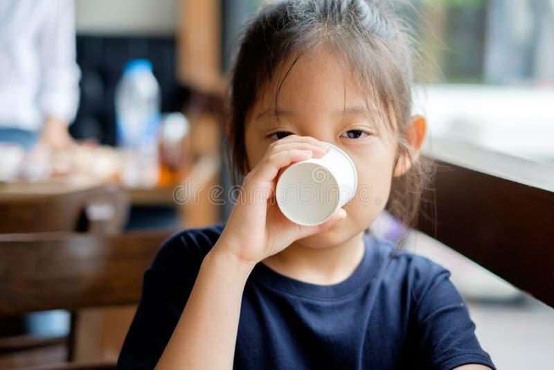 Asiatiskt barndricksvatten från den pappers- koppen royaltyfri bild