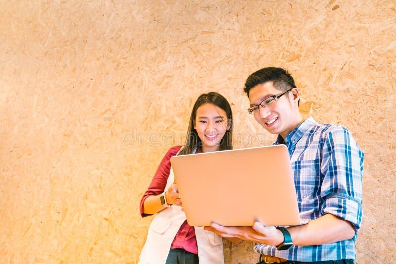 Asiatiskt coworker- eller högskolestudentlag som tillsammans använder bärbar datordatoren på kontoret eller universitetsområdet L arkivbild