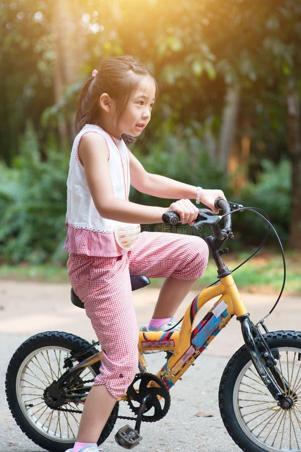Asiatiskt cykla för barn som är utomhus- royaltyfri foto