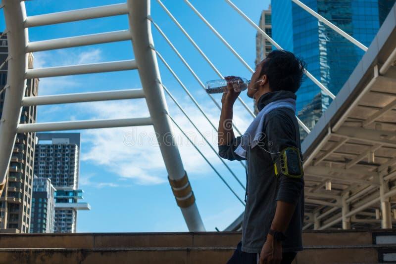 Asiatiskt dricksvatten för ung man efter övning inom staden arkivfoto