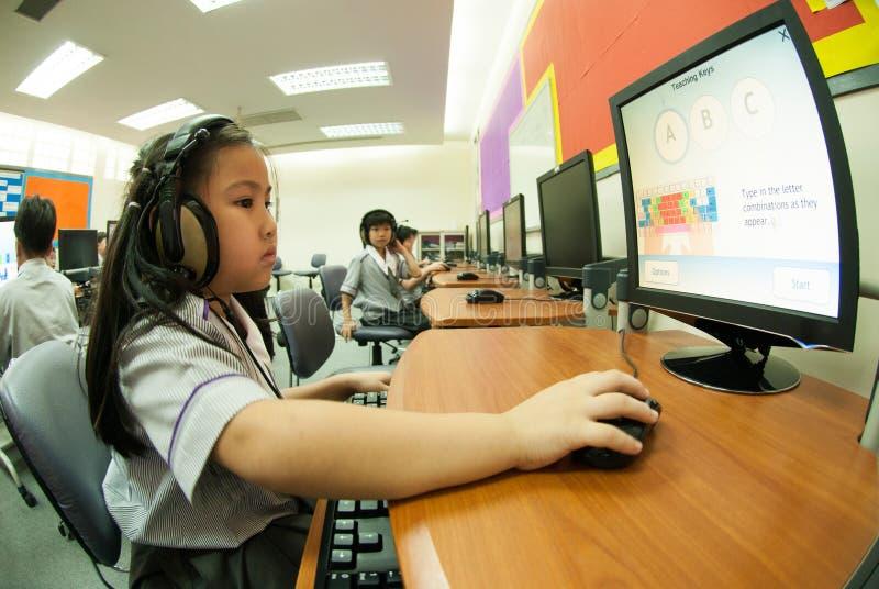 Asiatiskt elementärt barn som lär att använda datoren i klassrum royaltyfria bilder
