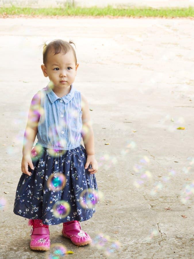 Asiatiskt flickaanseende bak att blåsa bubblor Rolig aktivitet Natu royaltyfria bilder