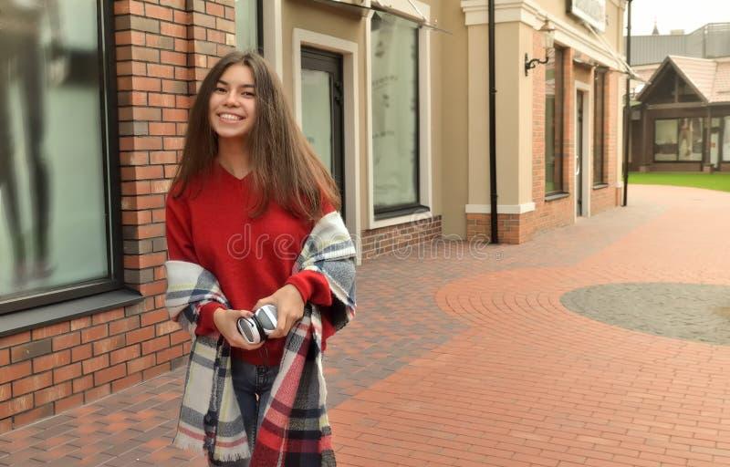 Asiatiskt flickaanseende vid byggnaden och le royaltyfri fotografi