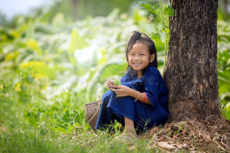 Asiatiskt flickasammanträdeleende på gräset i parkera arkivfoto