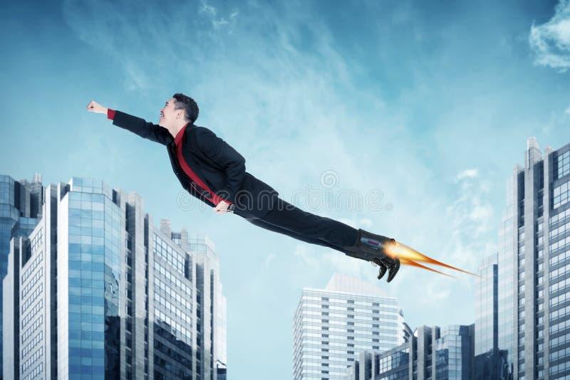 Asiatiskt flyg för affärsman med raket på skorna royaltyfri foto