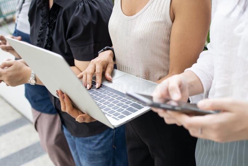 Asiatiskt folk för grupp som använder apparater smartphone och bärbar dator royaltyfri bild