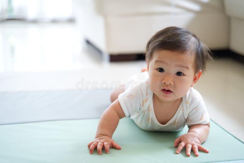 Asiatiskt gulligt behandla som ett barn att krypa på mjuk matta eller mattt hemma arkivbilder