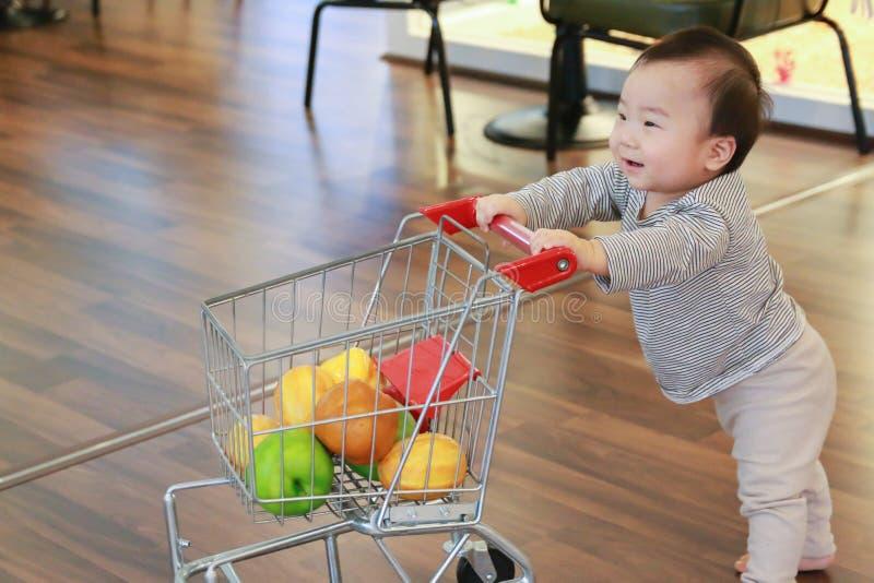 Asiatiskt gulligt behandla som ett barn att skjuta shoppa spårvagnleksaken fotografering för bildbyråer
