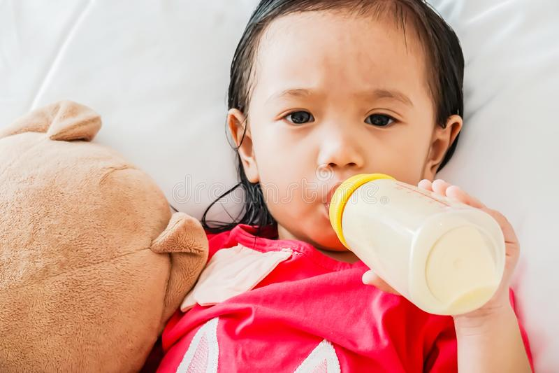 Asiatiskt gulligt behandla som ett barn flickan som att dricka mjölkar från flaskan och att sova på säng fotografering för bildbyråer