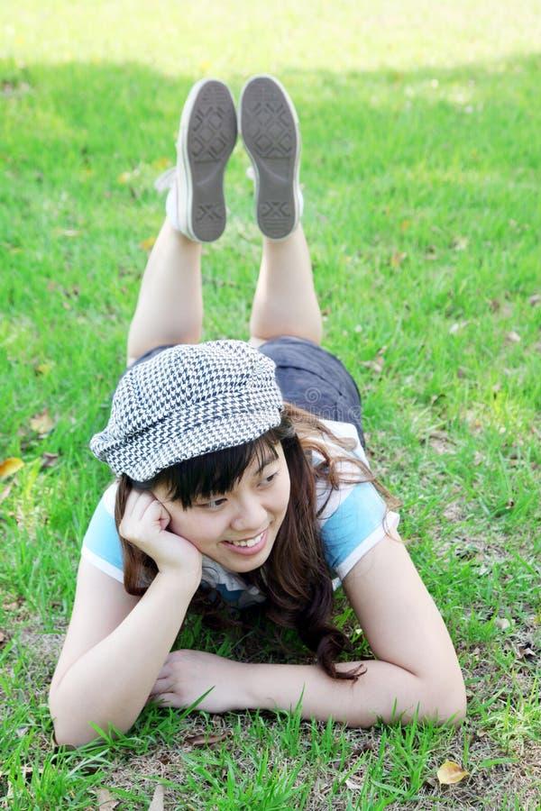 asiatiskt gulligt ligga för flickagräs arkivfoto