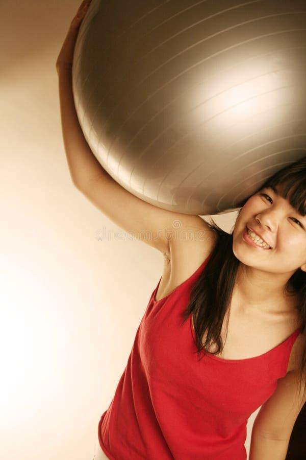 asiatiskt huvud för bollövningsflicka henne holding över arkivbild