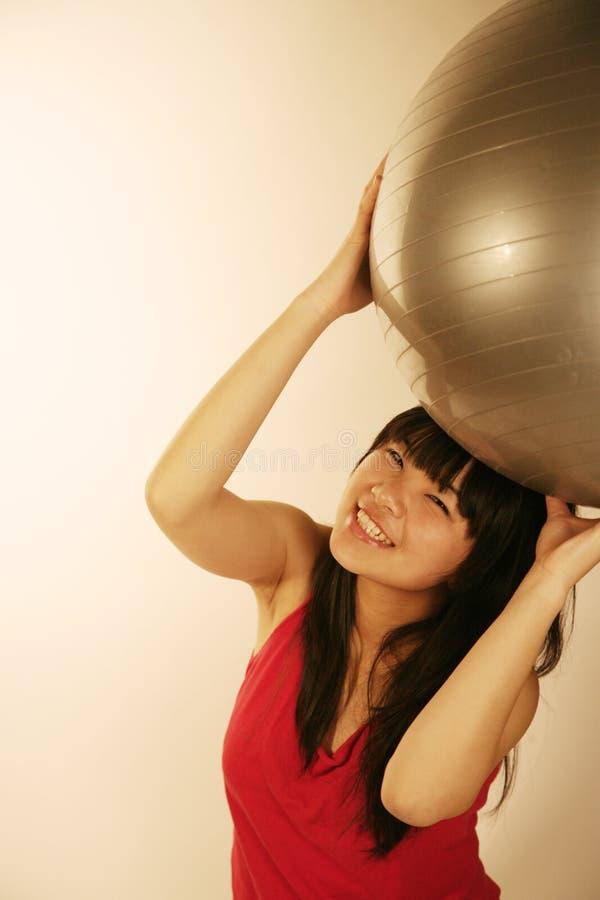 asiatiskt huvud för bollövningsflicka henne holding över fotografering för bildbyråer