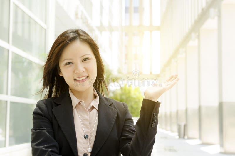 Asiatiskt innehav för hand för affärskvinna något arkivfoton