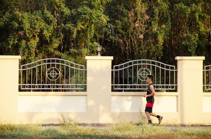 Asiatiskt jogga och övningen för thai folk körande i skymningtid på den offentliga trädgården parkerar i Nonthaburi, Thailand fotografering för bildbyråer