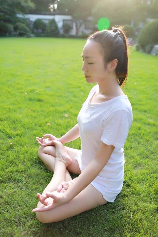 Asiatiskt kinesiskt liggande lägga på gräsgräsmatta som tänker för att göra yoga i solig dag för Forest Park solskensol royaltyfri bild