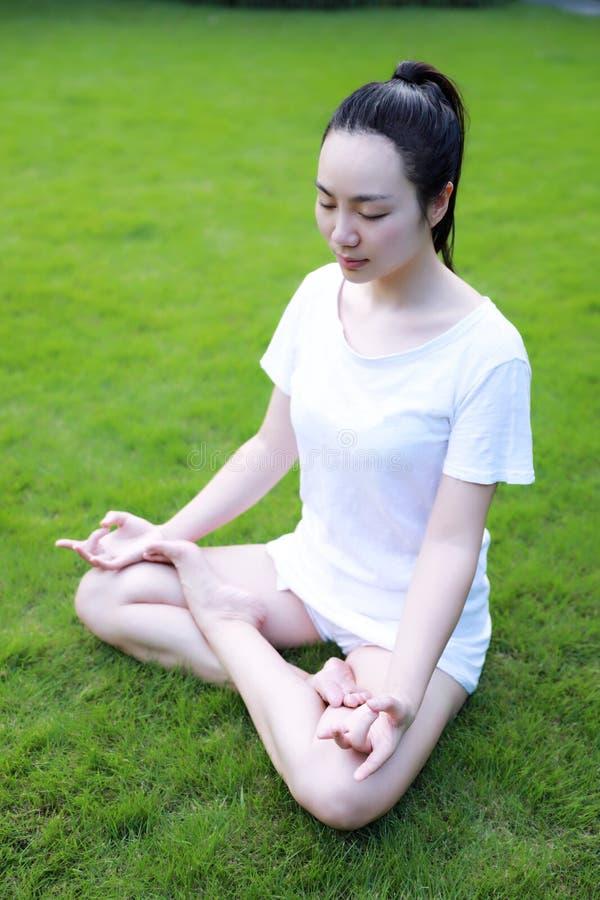 Asiatiskt kinesiskt liggande lägga på gräsgräsmatta som tänker för att göra yoga i solig dag för Forest Park solskensol arkivfoton