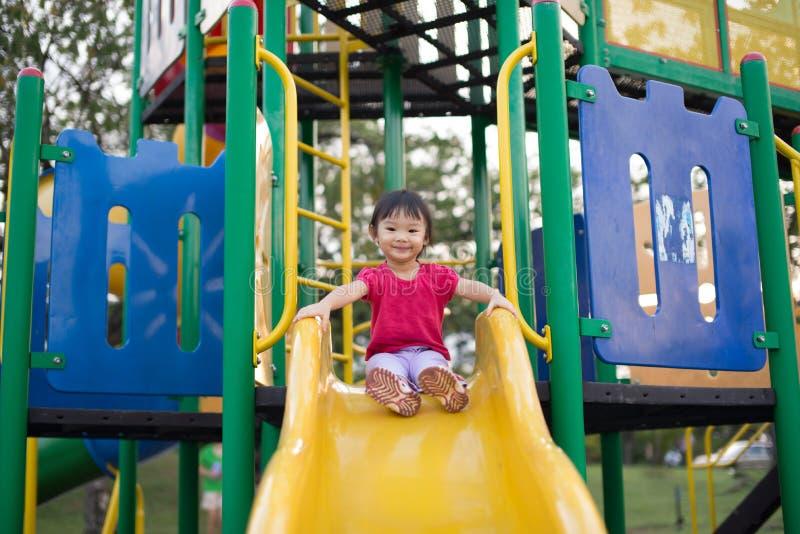 Asiatiskt kinesiskt två-år gammal flicka på en glidbana i lekplatsen royaltyfria foton
