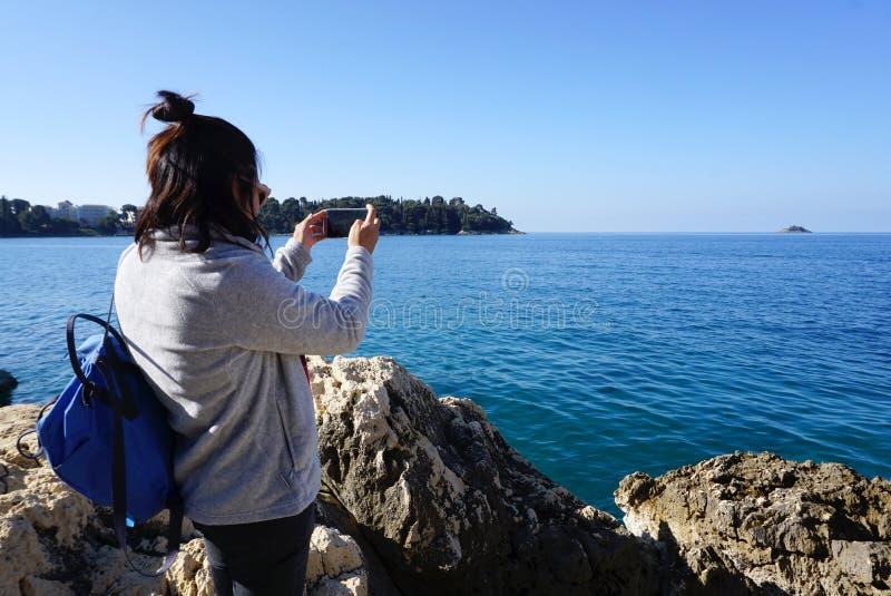 Asiatiskt kvinnaanseende på vagga som tar ett foto av Adriatiskt havet arkivfoton