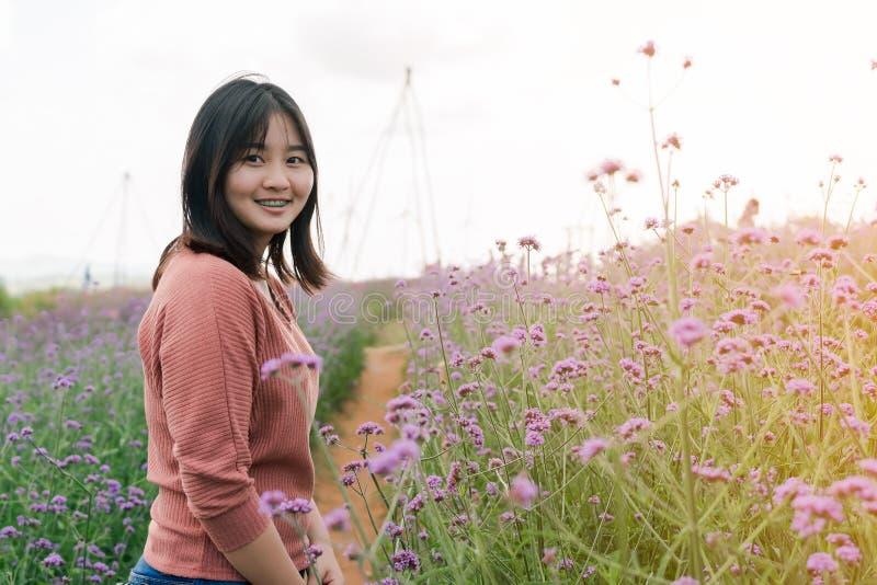 Asiatiskt kvinnaanseende som ler i en purpurfärgad blommaträdgård i mitt av det lyckliga uttryckt för dimma och för morgonsolljus royaltyfria bilder