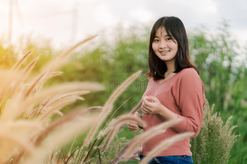 Asiatiskt kvinnaanseende som ler i fälten av brunt gräs i morgonsolen med en lycklig framsida royaltyfri foto