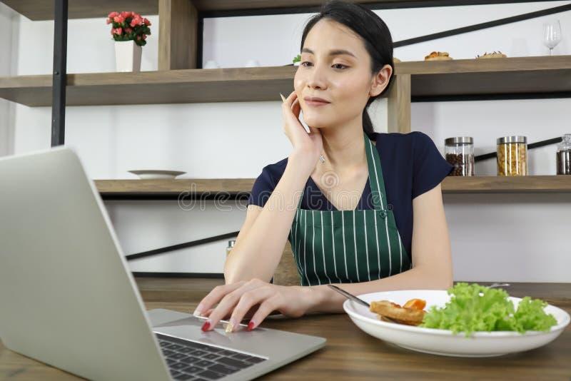 Asiatiskt kvinnaarbete för härlig ung entrpreneur med bärbara datorn med leende arkivbild