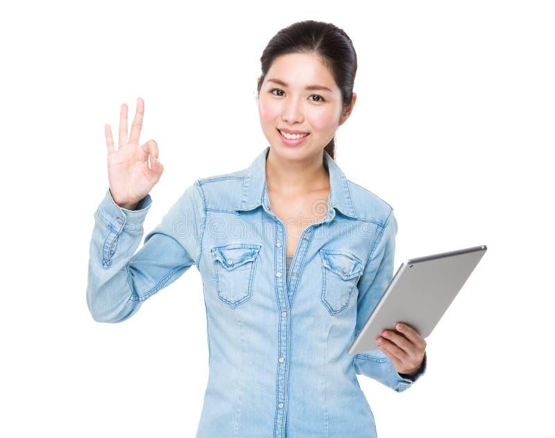 Asiatiskt kvinnabruk av den digitala minnestavlan och det ok tecknet gör en gest royaltyfri fotografi