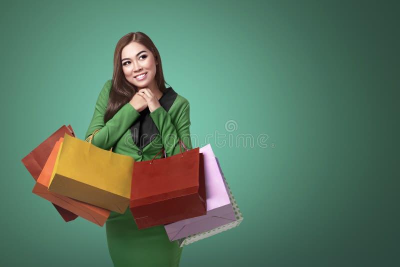 Asiatiskt kvinnainnehav i henne händer många som shoppar färgrika påsar fotografering för bildbyråer